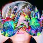 child with tie-dyed hands